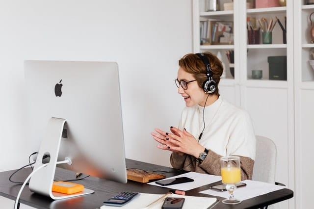 Mujer trabajando en computadora hablando por telefono
